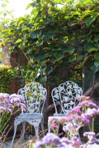 Cast iron chairs in cottage garden