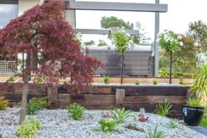 timber retaining wall with pebble rock garden